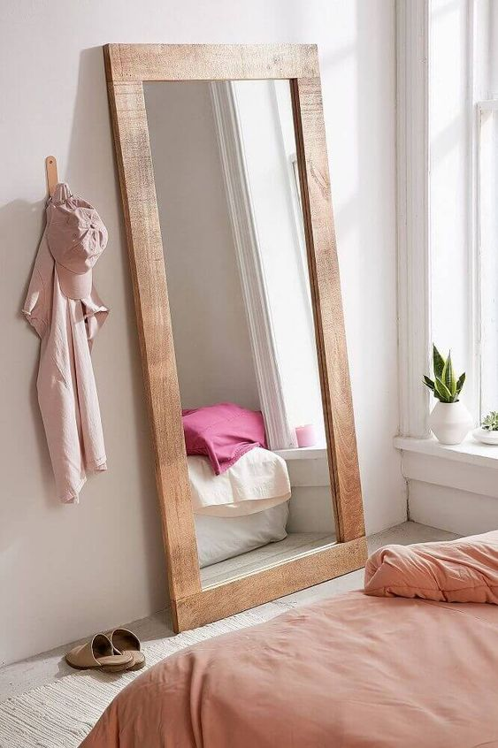 Espelho no chão com moldura de madeira.
