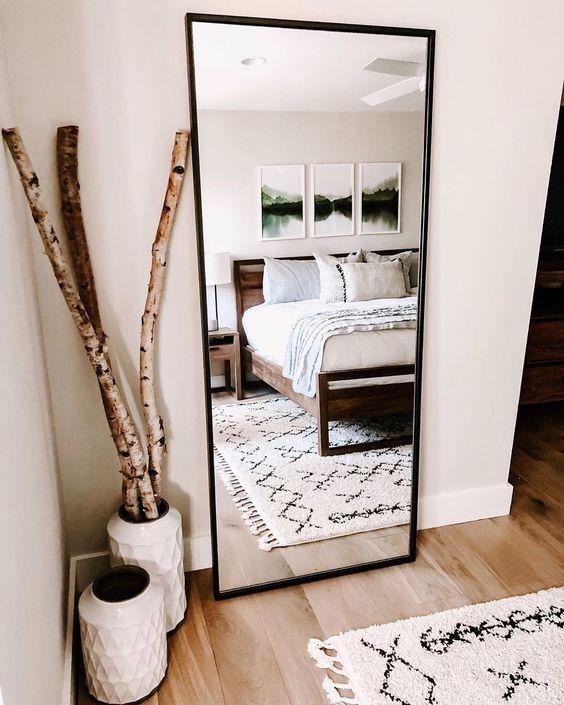 Espelho para quarto refletindo a cama.