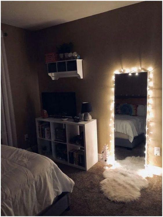 Espelho iluminado com tapete no chão.