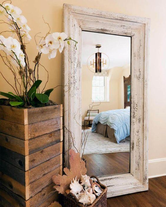 Espelho com moldura de madeira branca.