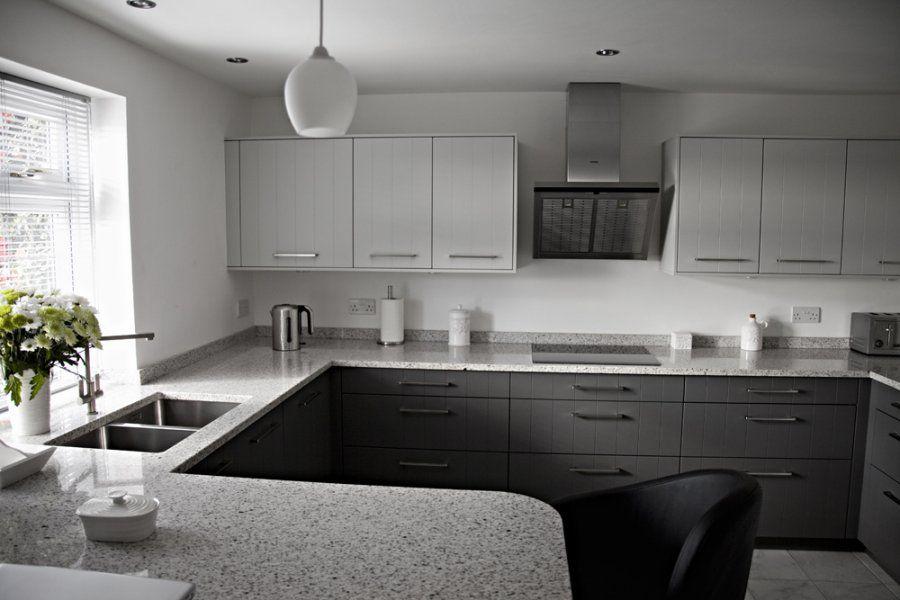 Cozinha cinza e moderna com bancada de granito branco polar.