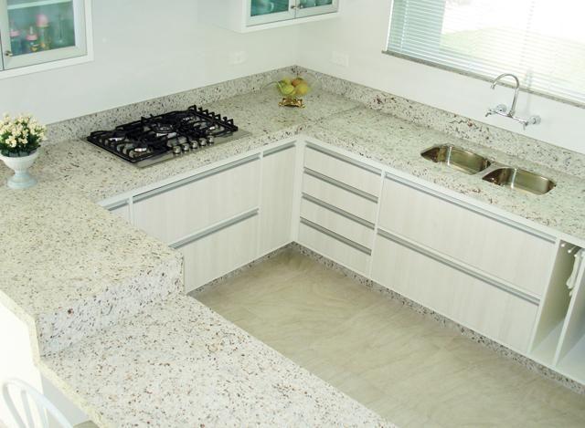 Cozinha em U com bancada de granito branco marfim.