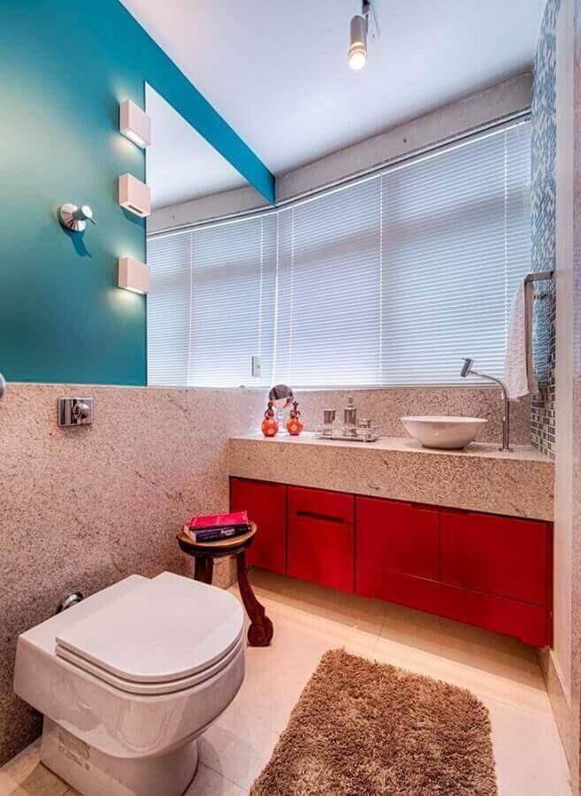 Lavabo decorado com armário vermelho.
