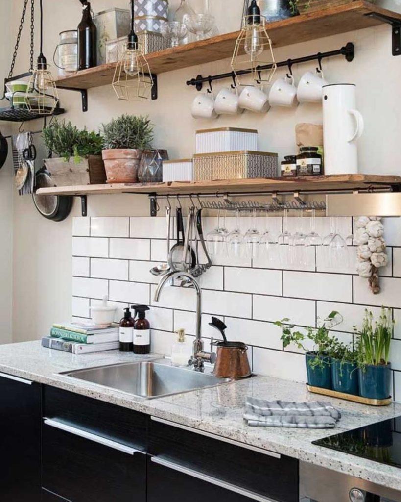 Cozinha moderna com armários pretos e azulejos de tijolinho branco.