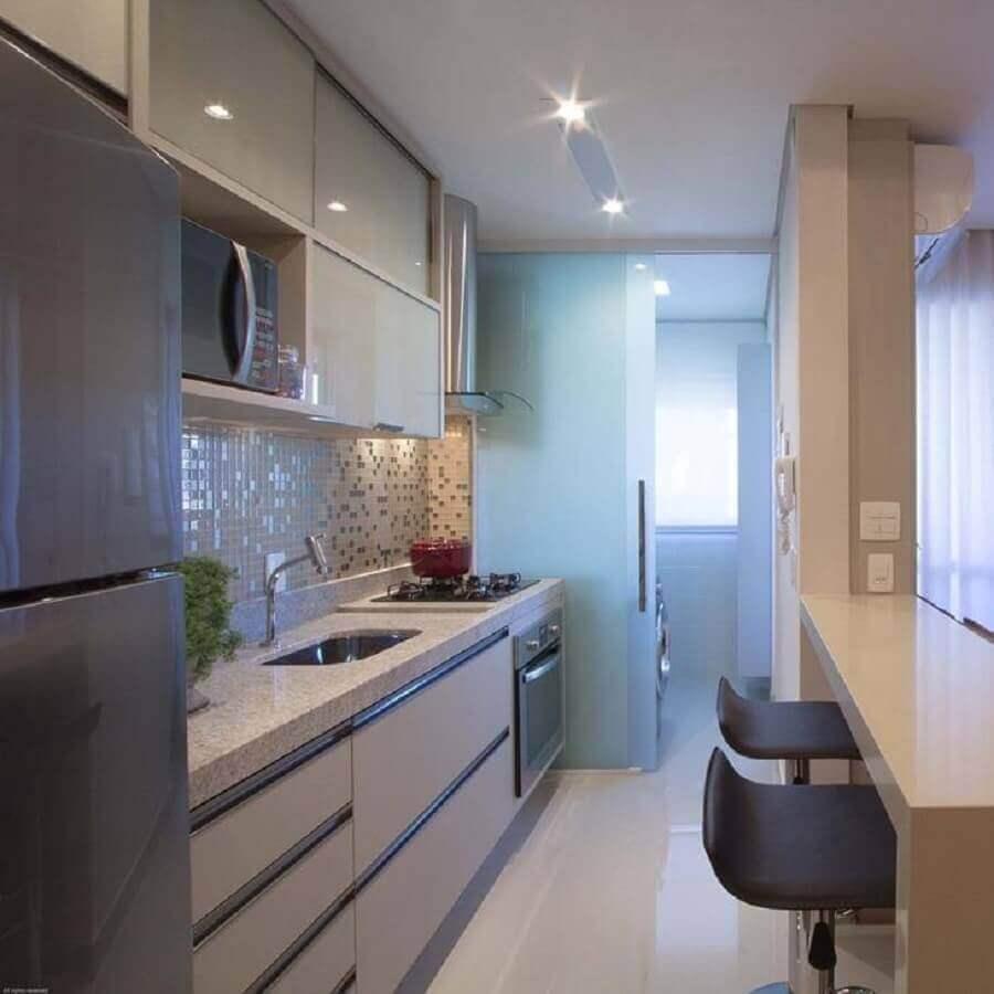 Cozinha americana com bancada de granito branco.