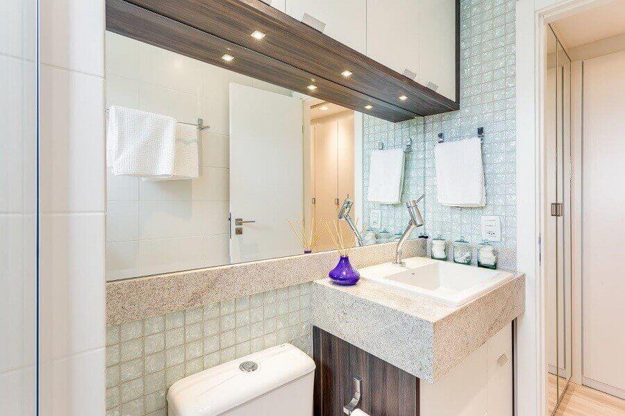 Banheiro pequeno com pia de granito branco.