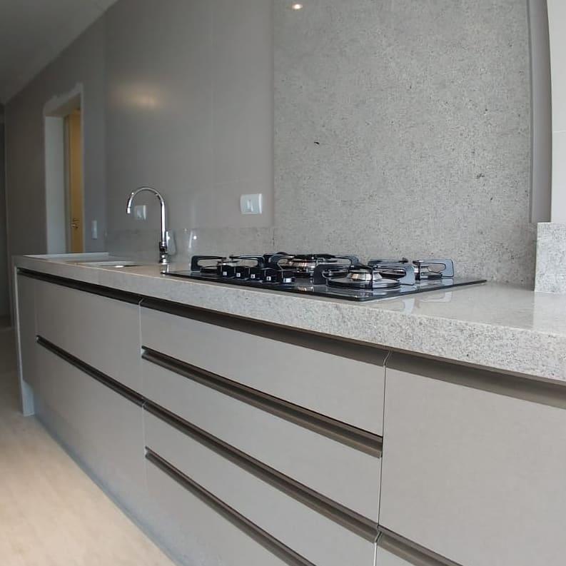 Cozinha  simples com cooktop e bancada de granito branco.