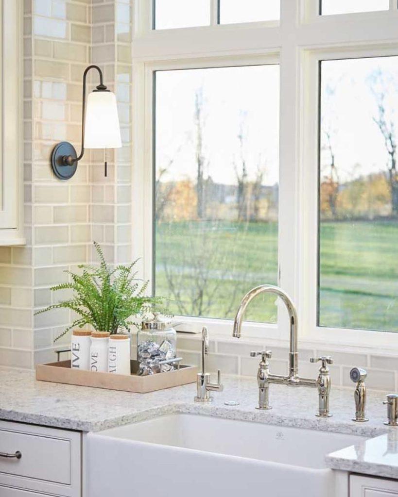 Cozinha com decoração clean e bancada de granito branco.