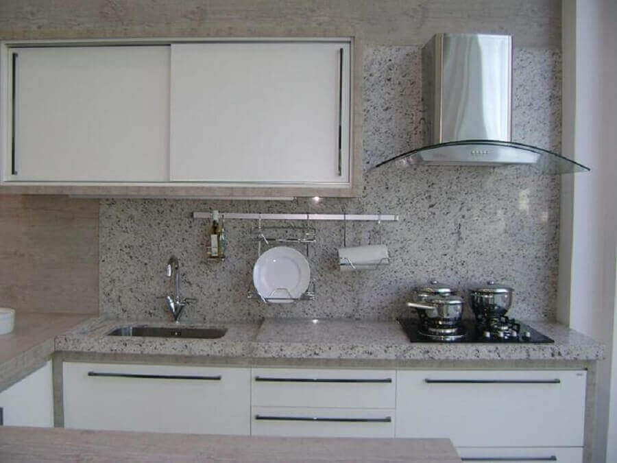 Cozinha em U com bancada de granito branco.