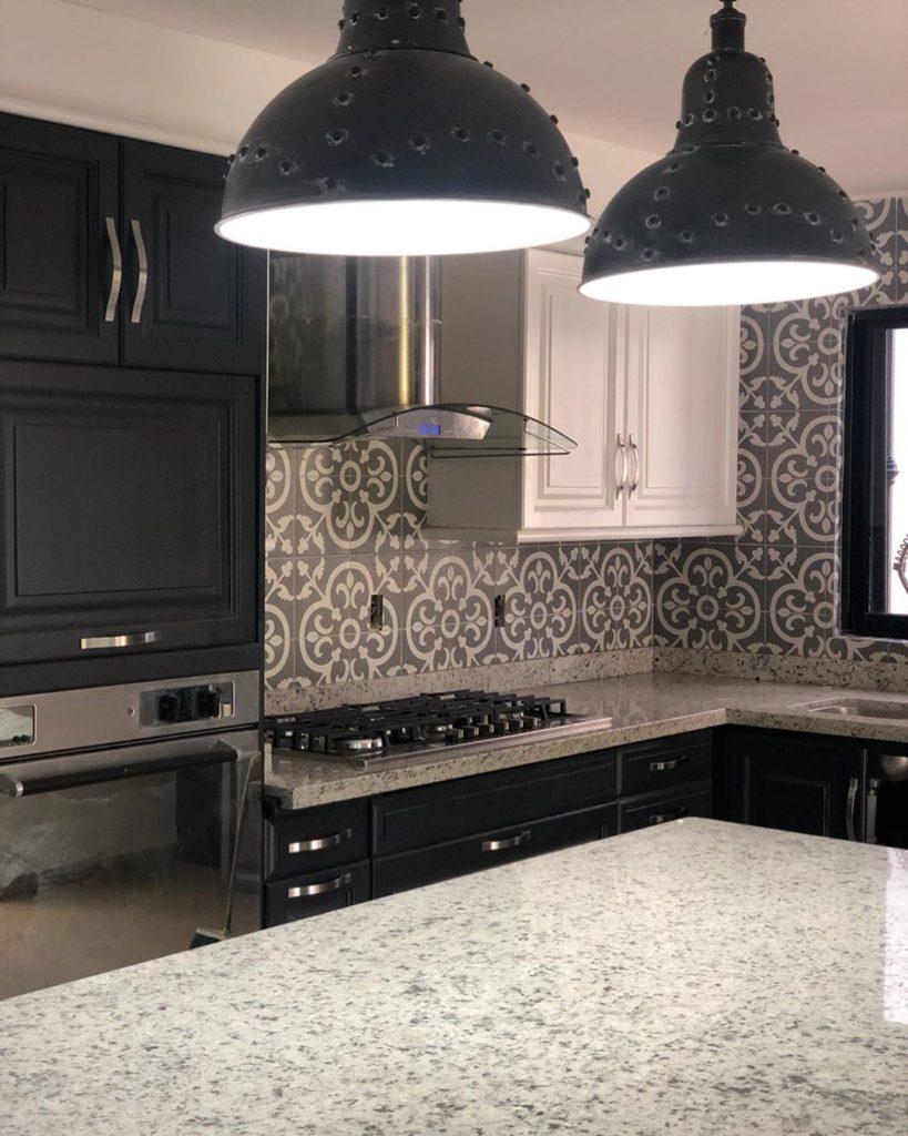 Cozinha moderna com armários pretos e ladrilhos hidráulicos.