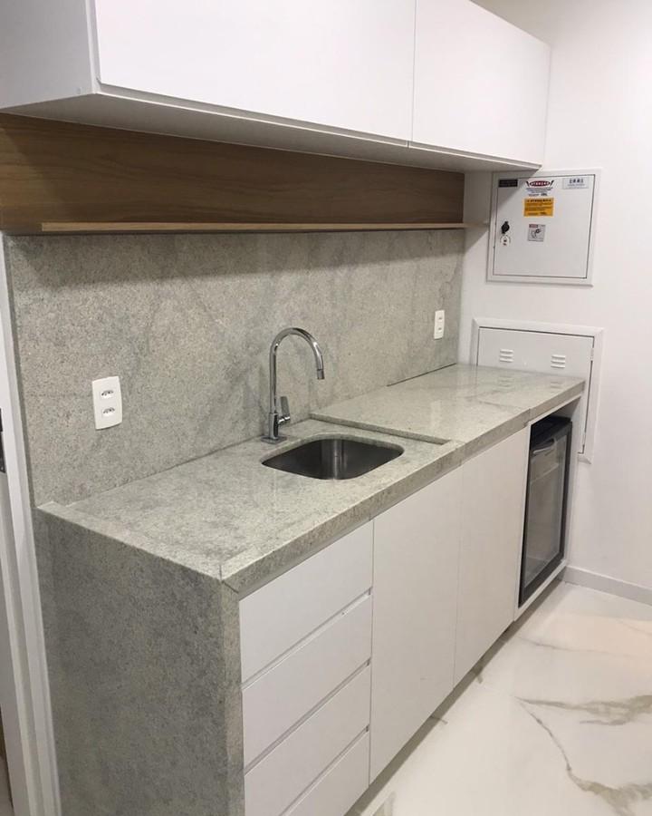 Cozinha pequena simples com bancada de granito branco.