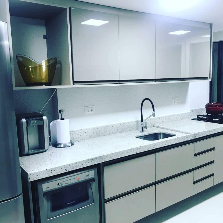 Cozinha pequena com bancada de granito branco.