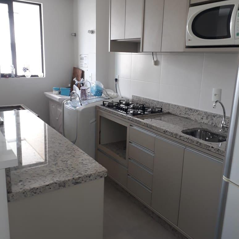 Cozinha pequena simples com armários neutros.