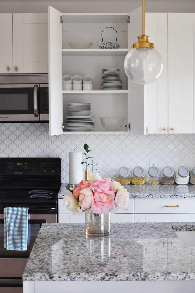 Cozinha clean com armários com puxadores dourados.