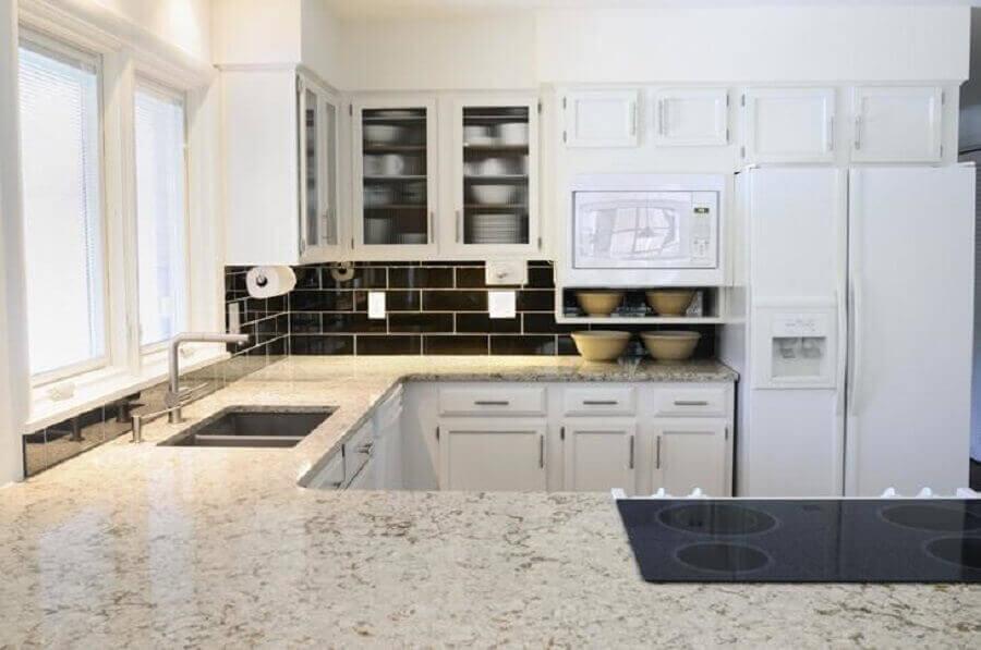 Cozinha em U com azulejo de tijolinho preto.