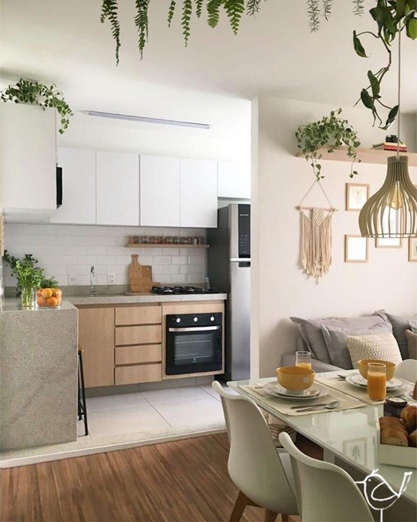 Cozinha em L com bancada de granito branco.