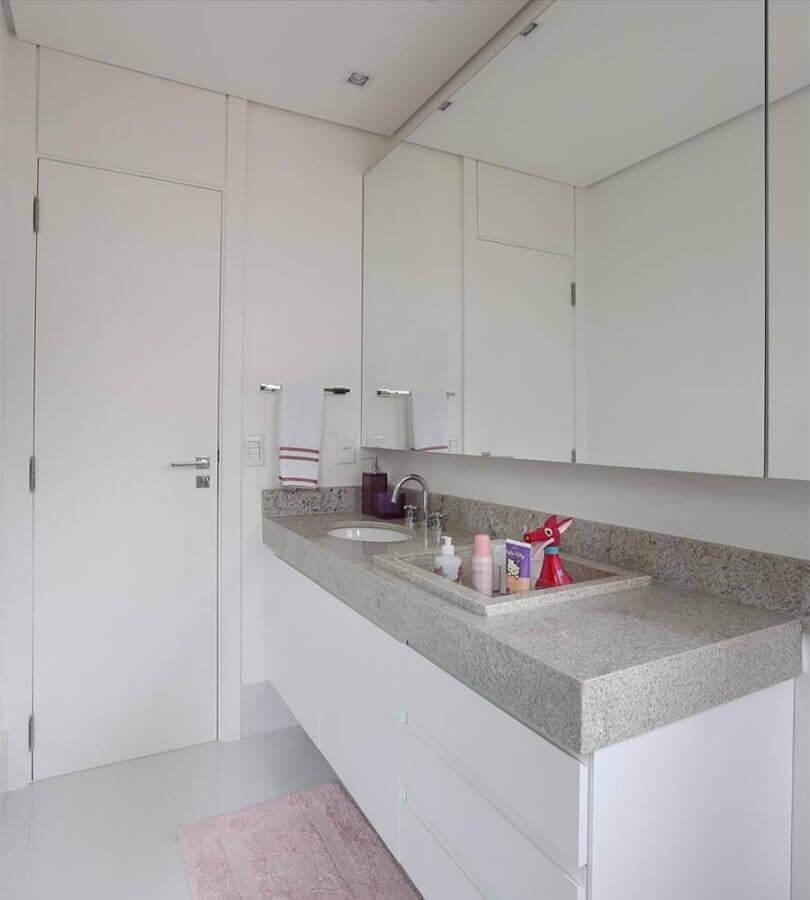 Banheiro com granito branco e armários modernos.