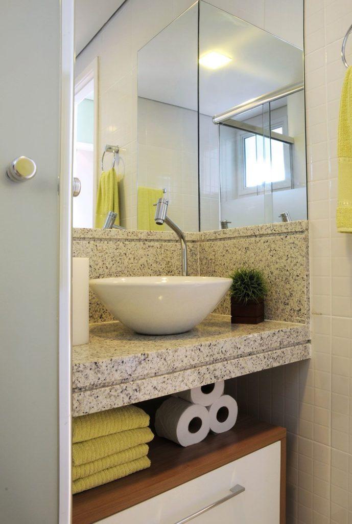 Banheiro pequeno com bancada de granito branco.