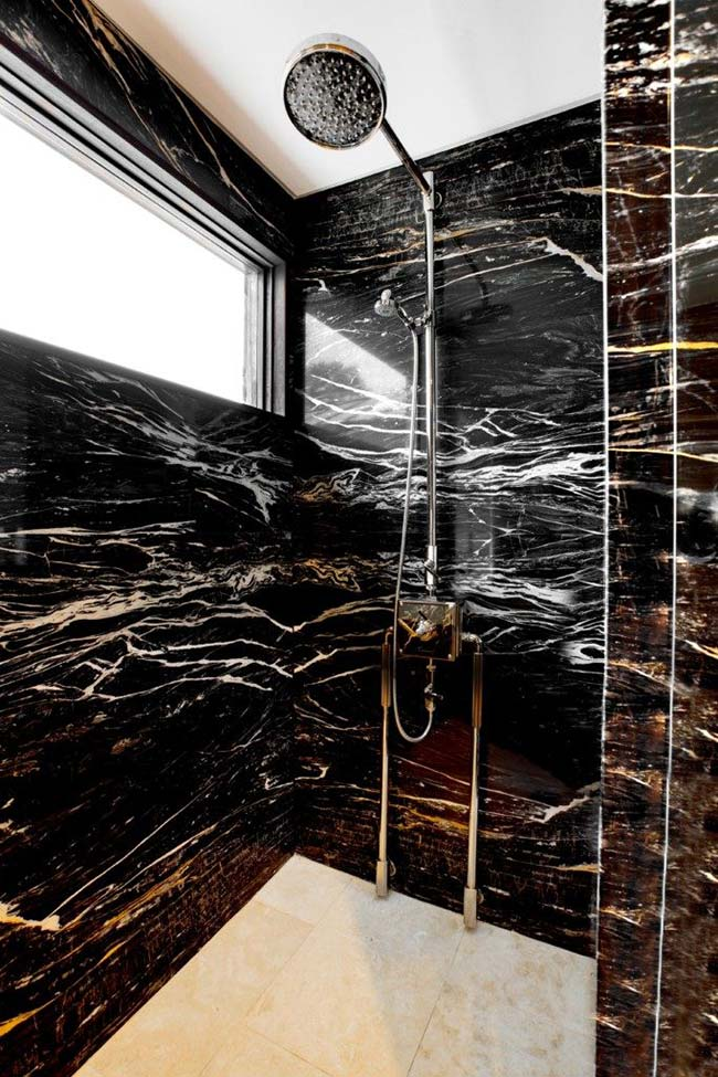Banheiro luxuoso com revestimento de granito preto indiano.