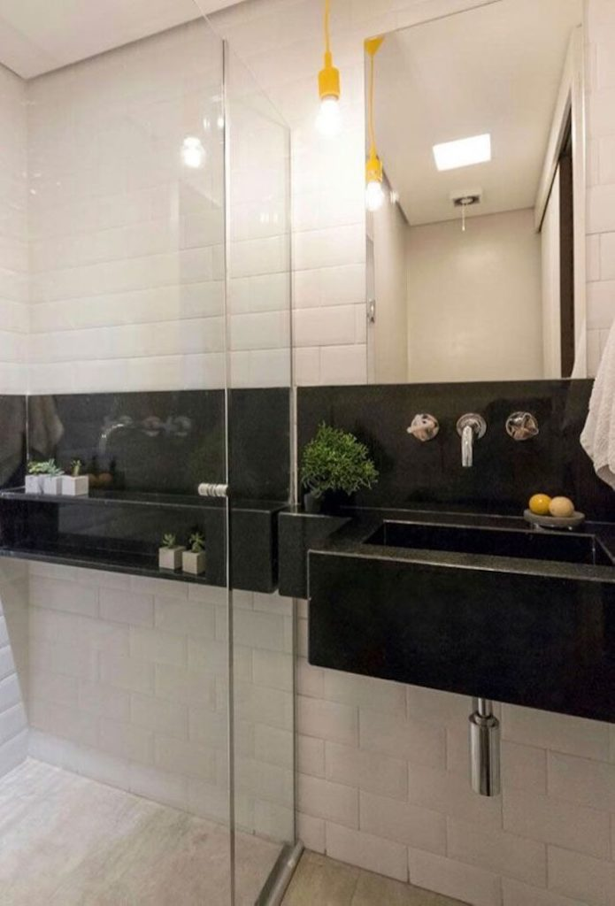 Banheiro pequeno com revestimento de tijolinho branco.