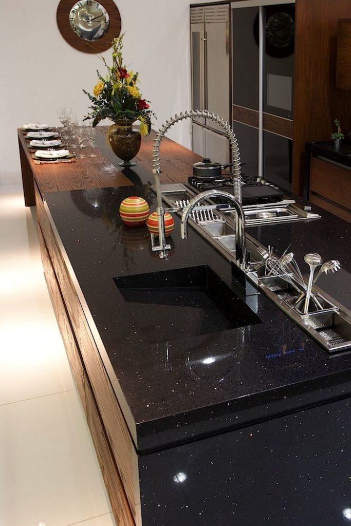 Cozinha com ilha com pia esculpida em granito preto stella.