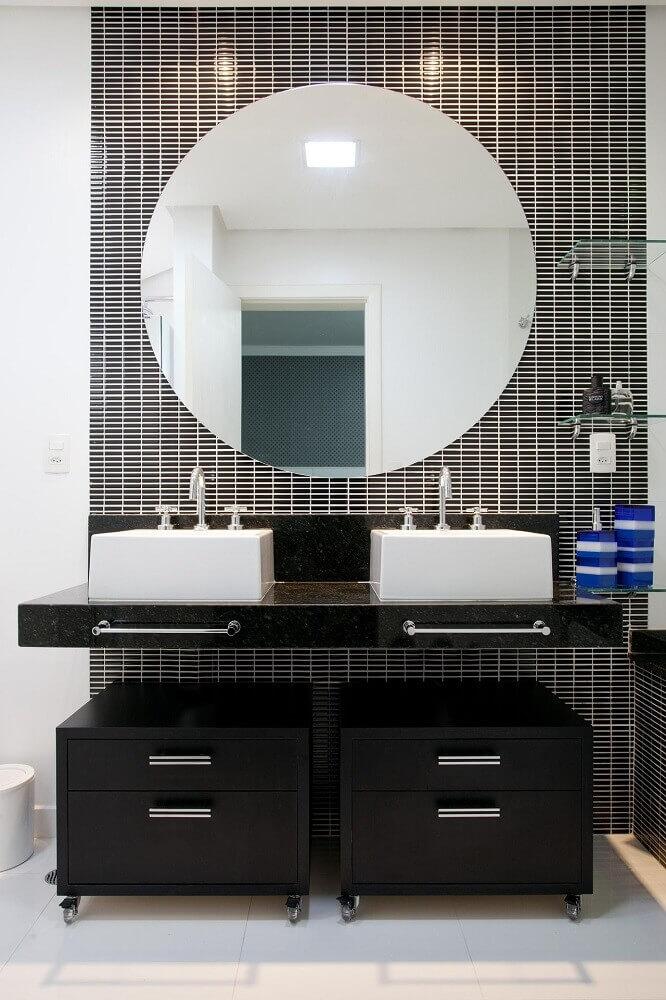 Banheiro moderno com bancada de pia dupla e espelho redondo.