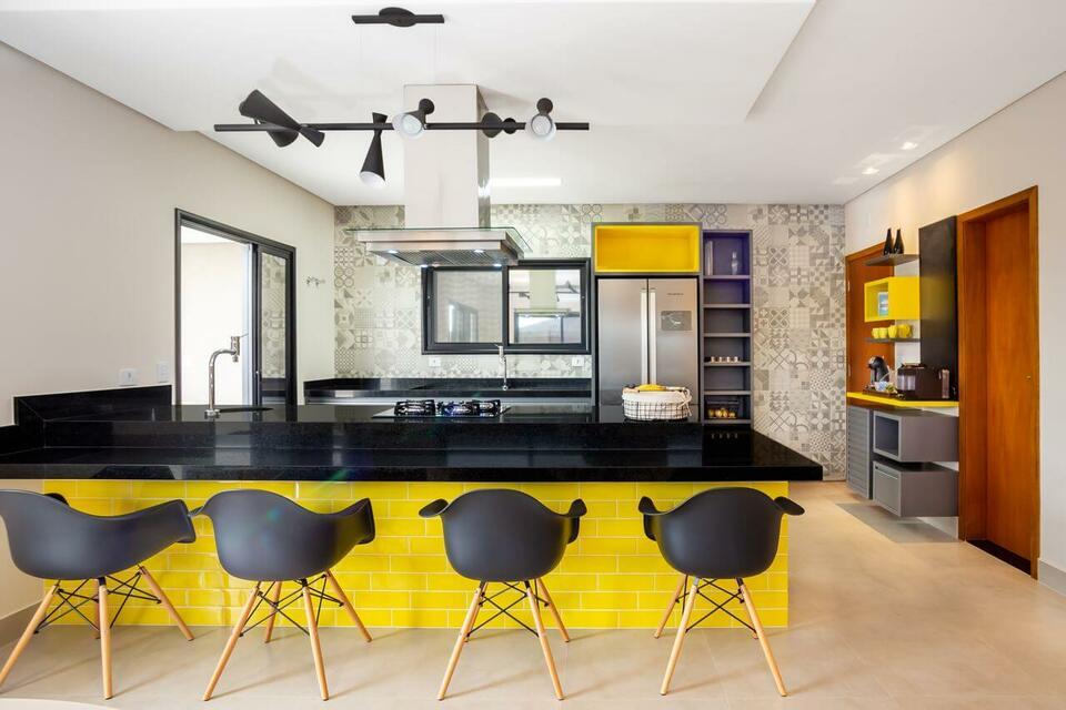 Cozinha planejada ampla com azulejo de tijolinho amarelo.