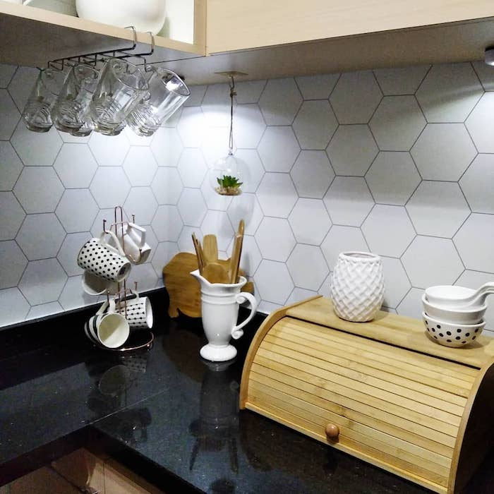 Bancada decorada e azulejo hexagonal branco.