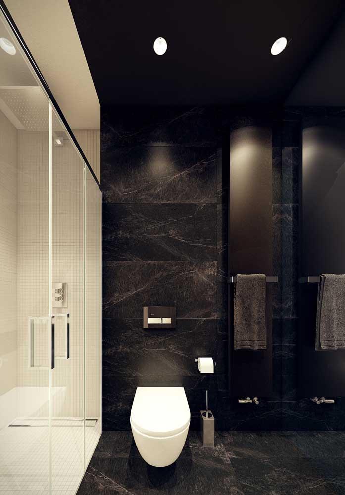 Banheiro luxuoso com revestimento de granito preto.