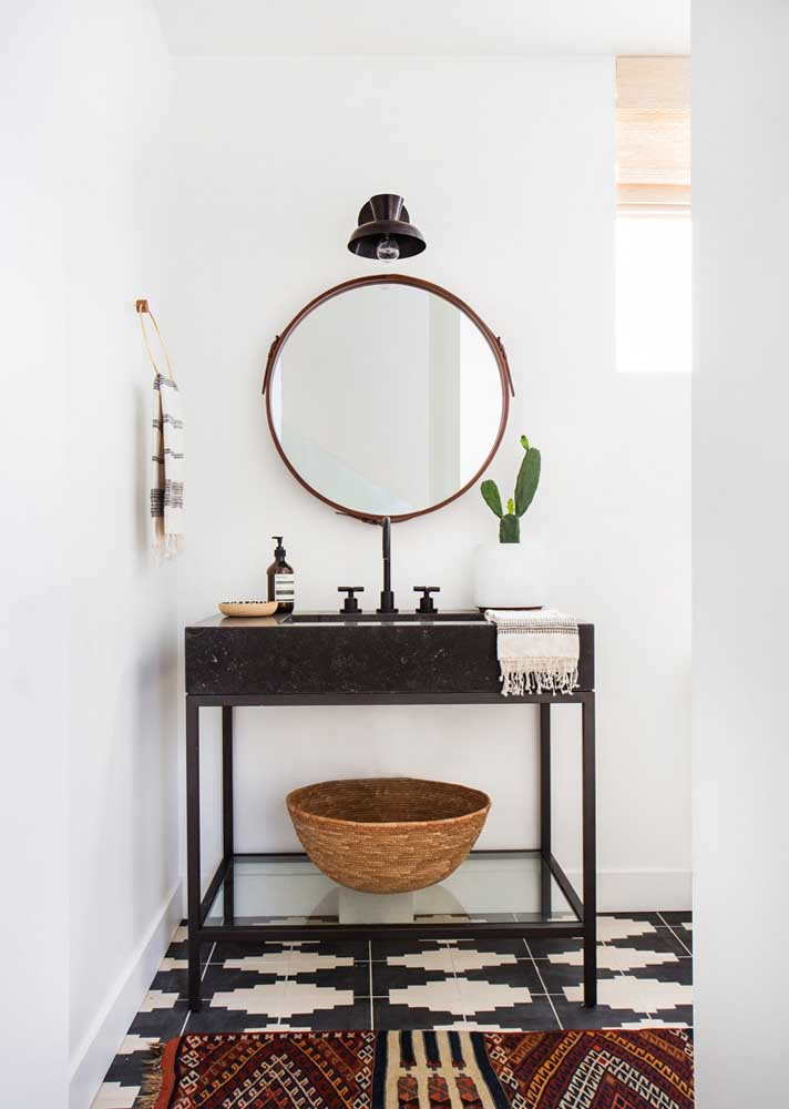 Banheiro moderno com decoração escandinava e espelho redondo.