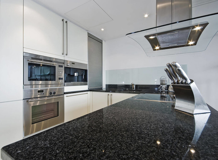Cozinha em U com armários brancos e granito preto.