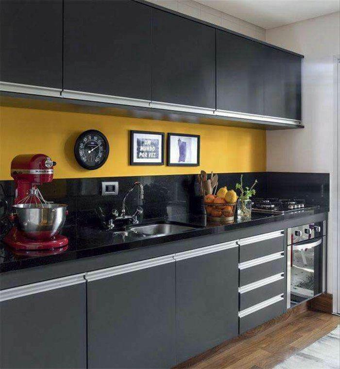 Cozinha pequena com armários pretos e parede amarela.
