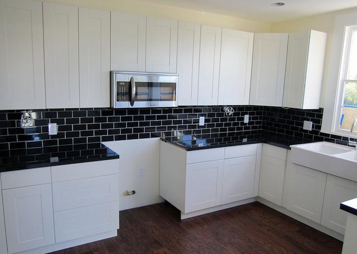 Cozinha branca com azulejo de tijolinho preto.