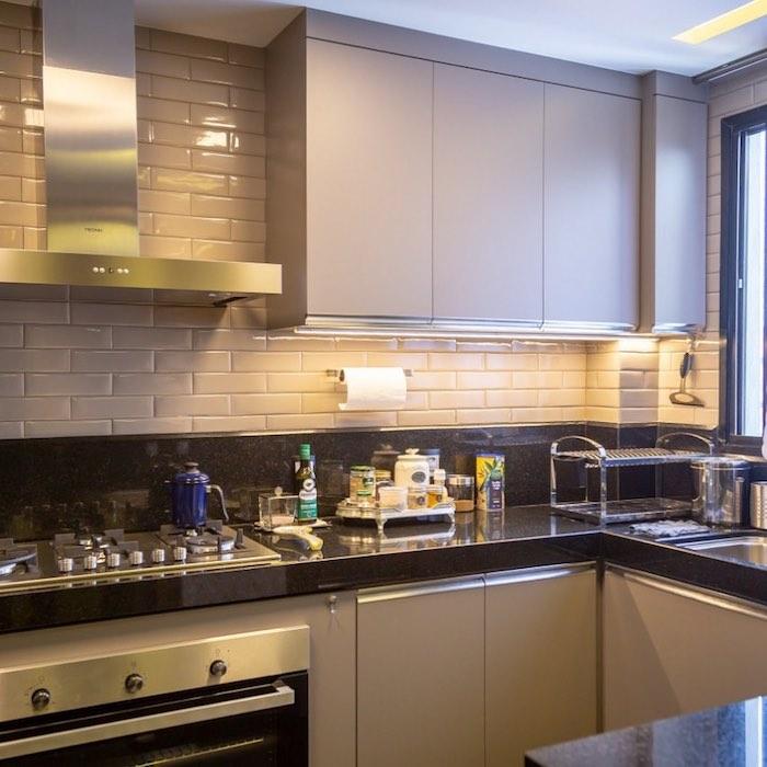 Cozinha simples com armários bege e bancada de granito preto.