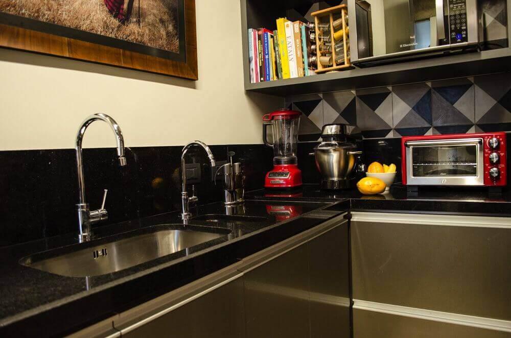 Cozinha simples com bancada de granito preto.