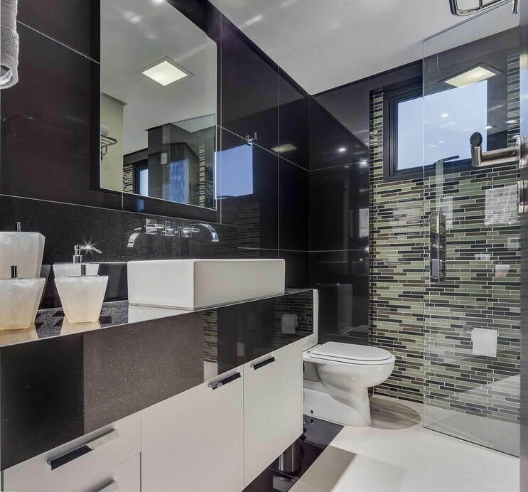 Banheiro luxuoso com revestimento de porcelanato e bancada de granito preto.