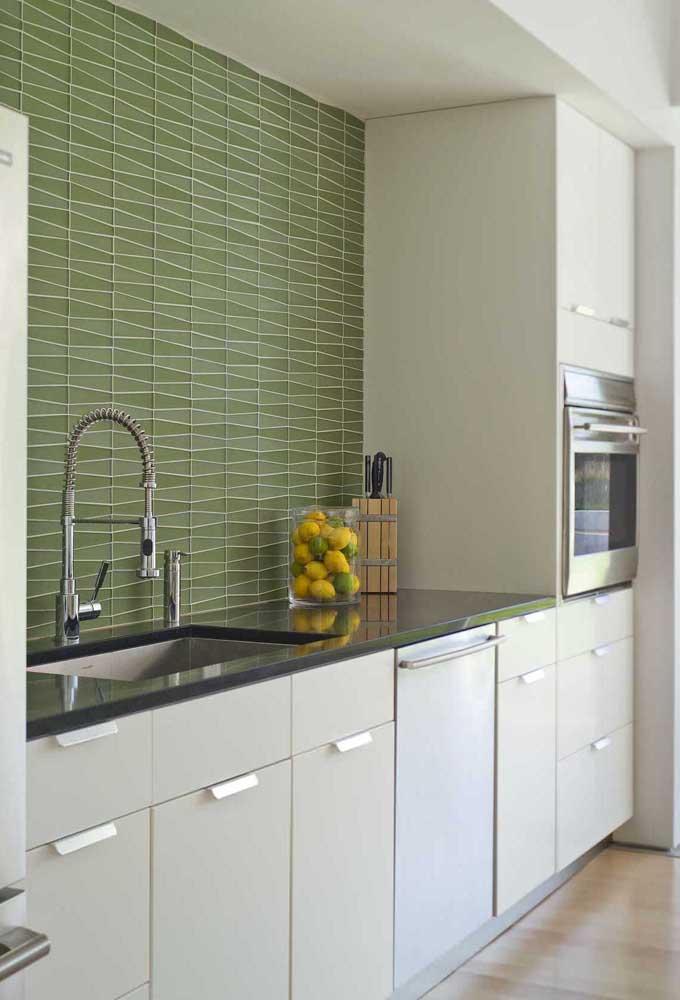 Cozinha simples com armários brancos e azulejos verdes.