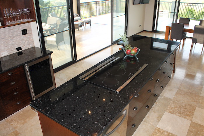 Cozinha com ilha moderna e bancada de granito preto stella.