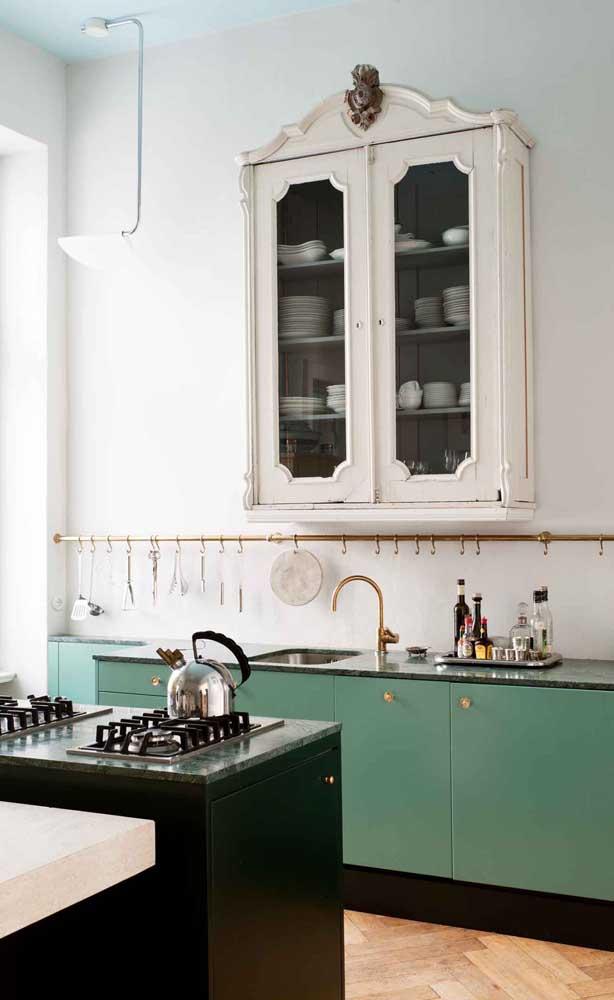Cozinha com armário verde e ilha com cooktop.