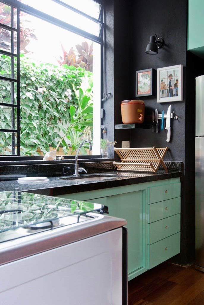 Cozinha pequena com armários verdes.
