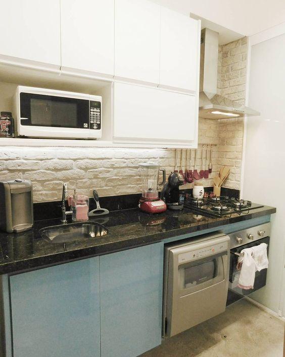 Cozinha pequena com armário azul e  parede com tijolinho branco aparente.