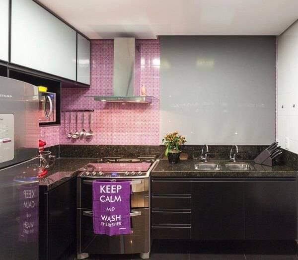 Cozinha pequena com azulejo rosa.