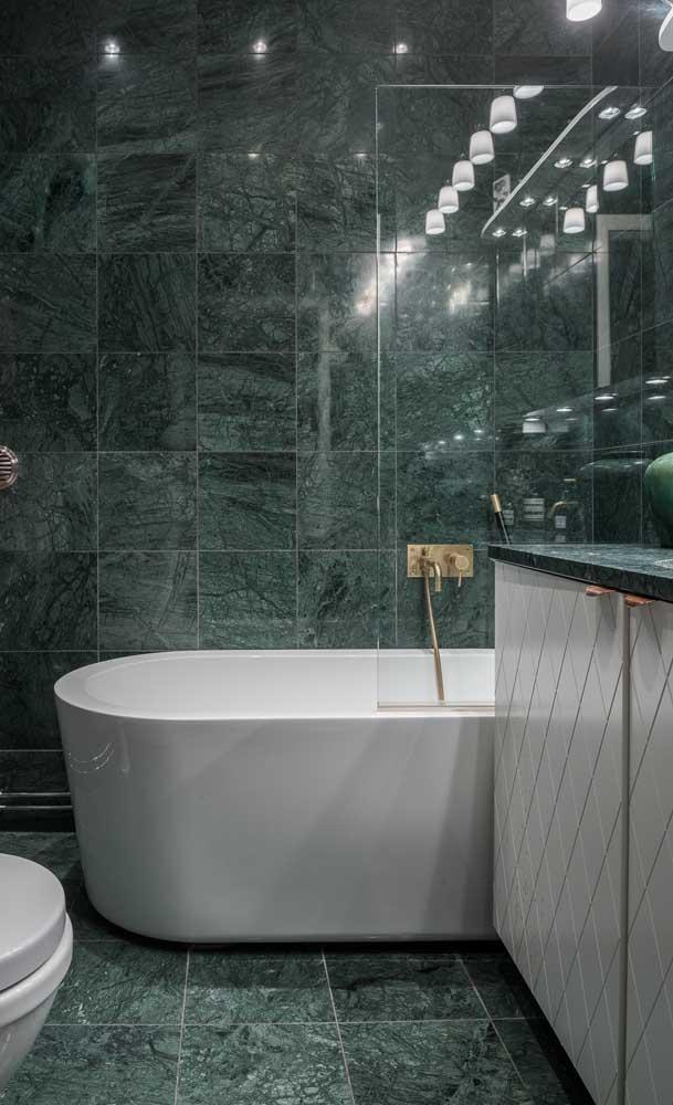 Banheiro luxuoso com revestimento de granito verde ubatuba.