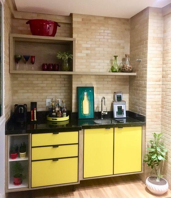 Varanda gourmet moderno com armário amarelo e tijolinho aparente.