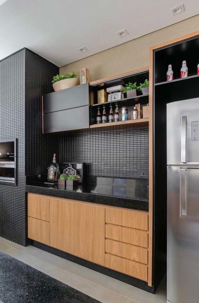 Varanda gourmet com pastilhas pretas e armários de madeira.