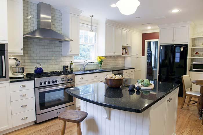 Cozinha com ilha e armários brancas.