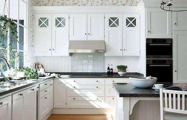 Cozinha branca com decoração clásssica.