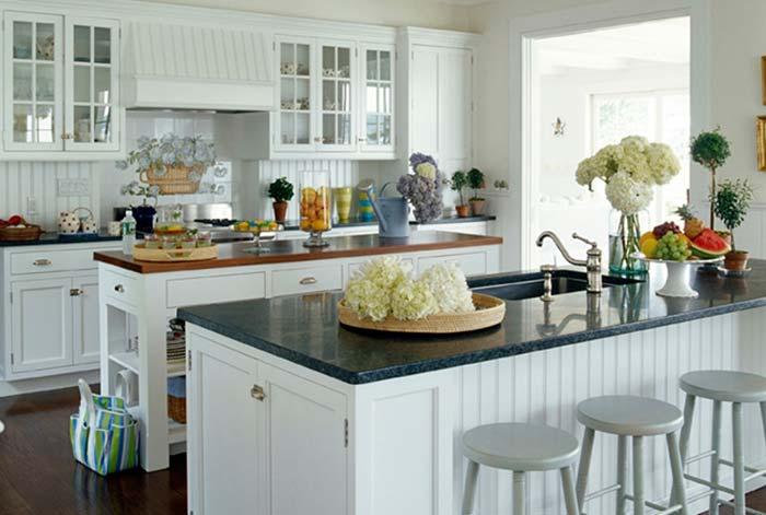 Cozinha com ilha grande com armários brancos.