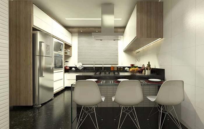 Cozinha em L com mesa de vidro.