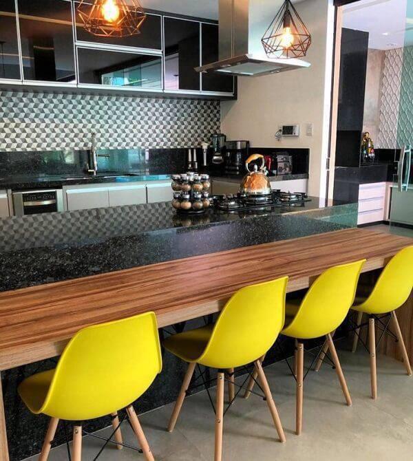 Cozinha com ilha e cadeiras de amarelas.
